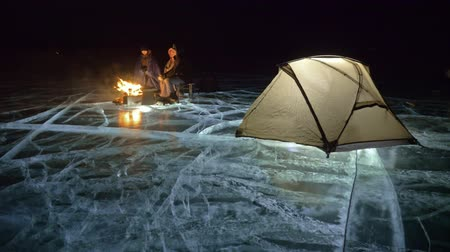kamp ateşi : Three travelers by fire right on ice at night. Campground on ice. Tent stands next to fire. Lake Baikal. Nearby there is car. People are warming around campfire and are dressed in sleeping bags. This is family consisting of father, mother and son.