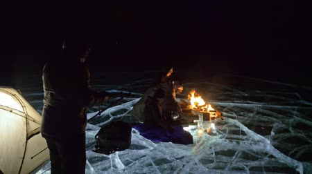 ağarmış : Four travelers by fire right on ice at night. Campground on ice. Tent stands next to fire. Lake Baikal. Nearby there is car. People are warming around campfire and are dressed in sleeping bags. Photographer in expedition shoots on camera in tripod. Stok Video