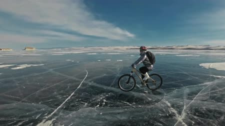 enduro : Woman is riding bicycle on the ice. The girl is dressed in a silvery down jacket, cycling backpack and helmet. Ice of the frozen Lake Baikal. The tires on the bicycle are covered with special spikes. The traveler is ride a cycle.