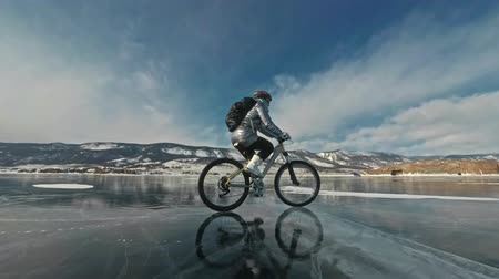 rampouch : Woman is riding bicycle on the ice. The girl is dressed in a silvery down jacket, cycling backpack and helmet. Ice of the frozen Lake Baikal. The tires on the bicycle are covered with special spikes. The traveler is ride a cycle.