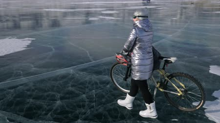 zíper : Woman is walking beside bicycle on the ice. The girl is dressed in a silvery down jacket, backpack and helmet. Ice of the frozen Lake Baikal. The tires on the bicycle are covered with special spikes. The traveler is ride a cycle. Vídeos