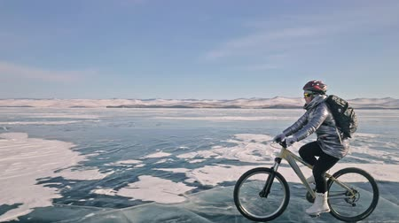 sırt çantasıyla : Woman is riding bicycle on the ice. The girl is dressed in a silvery down jacket, cycling backpack and helmet. Ice of the frozen Lake Baikal. The tires on the bicycle are covered with special spikes. The traveler is ride a cycle.