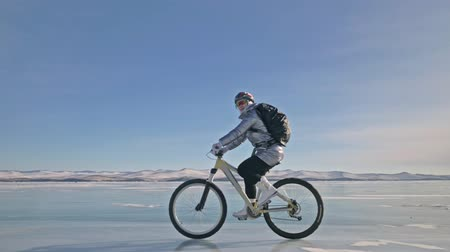 с шипами : Woman is riding bicycle on the ice. The girl is dressed in a silvery down jacket, cycling backpack and helmet. Ice of the frozen Lake Baikal. The tires on the bicycle are covered with special spikes. The traveler is ride a cycle.