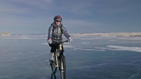 frozen lake : Woman is riding bicycle on the ice. The girl is dressed in a silvery down jacket, cycling backpack and helmet. Ice of the frozen Lake Baikal. The tires on the bicycle are covered with special spikes. The traveler is ride a cycle.