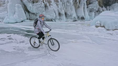 с шипами : Woman is riding bicycle near the ice grotto. The rock with ice caves and icicles is very beautiful. The girl is dressed in silvery down jacket, cycling backpack and helmet. The tires on covered with special spikes. The traveler is ride cycle.