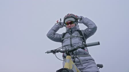 с шипами : Woman is wearing sports equipment. The girl is dressed in a silvery down jacket, cycling backpack and helmet. Ice of the frozen Lake Baikal. The tires on the bicycle are covered with special spikes. The traveler is ride a cycle.