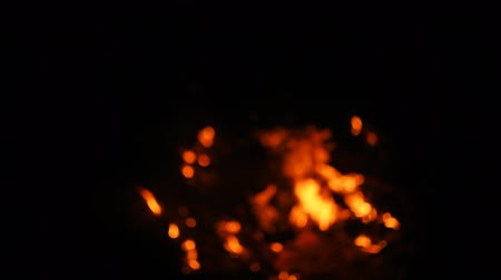 espaço de texto : Fire in nature. Bokeh from the fire. Blurred backgrounds. Space views. Sparks are beautifully flying right at you. Shooting speed 60fps, slow motion. Live shooting of the most beautiful flame.