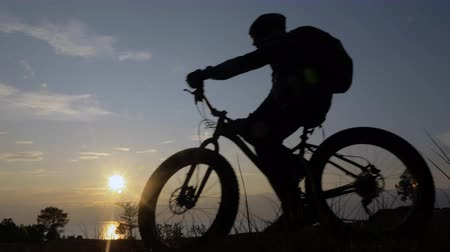 him : Fat bike also called fatbike or fat-tire bike in summer riding in the grass. The athlete passes in a frame silhouette against a beautiful sunset on the sea. Everything happens in deep grass.