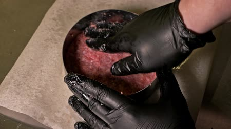 aço inoxidável : Cook makes meat medallions for burgers. Chef in black food gloves makes cutlet. Cutlets are leveled in steel ring in an even medallion. On top of pouring spices pepper and salt. Meat marbled beef lies on food paper and covered with plastic wrap. Stock Footage