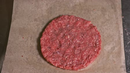 produkt : Cook makes meat medallions for burgers. Chef in black food gloves makes cutlet. Cutlets are leveled in steel ring in an even medallion. On top of pouring spices pepper and salt. Meat marbled beef lies on food paper and covered with plastic wrap. Dostupné videozáznamy