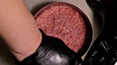 marmorizado : Cook makes meat medallions for burgers. Chef in black food gloves makes cutlet. Cutlets are leveled in steel ring in an even medallion. On top of pouring spices pepper and salt. Meat marbled beef lies on food paper and covered with plastic wrap. Stock Footage