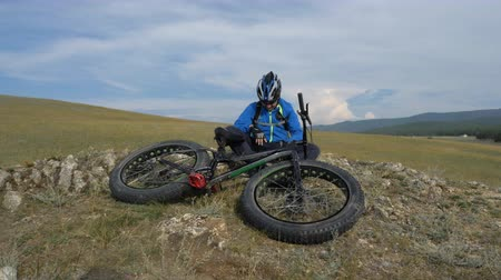 him : Fat bike also called fatbike or fat-tire bike in summer driving through the hills. The guy sits on a stony sandy and grassy hill after a trip. He rests and enjoys the fresh air. Stock Footage