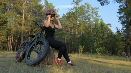 moto trials : Fat bike also called fatbike or fat-tire bike in summer riding in the forest. Beautiful girl and her bicycle in the forest. She sits on the stump and rests from the trip. Stock Footage