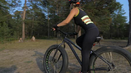she : Fat bike also called fatbike or fat-tire bike in summer riding in the forest. Beautiful girl and her bicycle in the forest. She rides next to the camera.