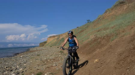 гелий : Fat bike also called fatbike or fat-tire bike in summer driving on the road. The guy rides by the hill on a sand clay path, behind him the shore by the sea. Slow motion shooting 180fps.