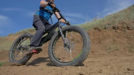 slough : Fat bike also called fatbike or fat-tire bike in summer driving on the road. The guy rides by the hill on a sand clay path. The bicycle is allowed into the drift. Slow motion shooting 180fps. Stock Footage