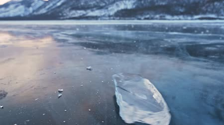camera rotation : The ice floe rotates on the ice against the background of the amazing mountain landscape. Slow motion. The camera moves behind the ice. A piece of icy is very beautifully spinning on ice with magical cracks.