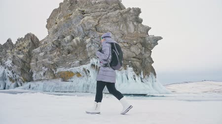 rachaduras : Travel of woman on ice of Lake Baikal. Trip to winter island. Girl is walking at foot of ice rocks. Traveler looks at beautiful ice grotto. Hiker wears sports glasses, silver jacket, backpack. Extreme trek and walk. Backpacker is resting on nature.