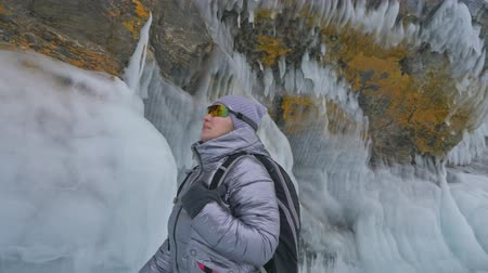 gruta : Travel of woman on ice of Lake Baikal. Trip to winter island. Girl is walking at foot of ice rocks. Traveler looks at beautiful ice grotto. Hiker wears sports glasses, silver jacket, backpack. Extreme trek and walk. Backpacker is resting on nature.