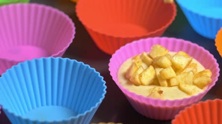panelas : Cooking cupcake from light dough with apples. Muffins pour out in silicone tray. Pouring dough cake into muffin baking dish. Sprinkle the top of the cupcake with grated chocolate. Baking dish colorful. Shooting in 180fps.