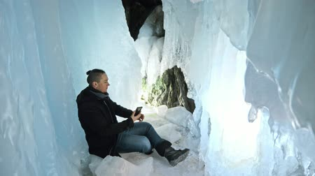 rampouch : Man communicates in smartphone in an ice cave. Around the mysterious beautiful ice grotto. User communicates in social networks in mobile, takes photo and makes selfie on the phone. He crazy strange funny hipster in black coat and fashionable hairdo.