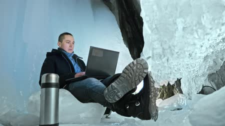 gruta : Man is sit on the internet in laptop in an ice cave. Around the mysterious beautiful ice grotto. User communicates in social networks. He crazy strange hipster in black coat and fashionable hairdo. Guy is warming himself with the coffee from thermos.