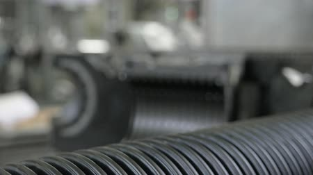granulação : Manufacture of plastic water pipes. Manufacturing of tubes to the factory. The process of making plastic pipes on the machine tool with the use of water and air pressure. Special corrugated forms of the workpiece are used.