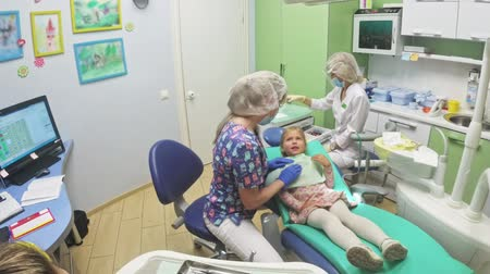 вылеченный : Child with a mother at a dentists reception. The girl lies in the chair, behind her mother. The doctor works with an assistant. Procedure for drilling a tooth. Setting a temporary seal. Using the x-ray machine. Стоковые видеозаписи