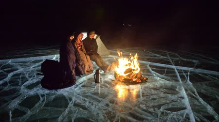 zmrazit : Three travelers by fire right on ice at night. Campground on ice. Tent stands next to fire. Lake Baikal. Nearby there is car. People are warming around campfire and are dressed in sleeping bags. This is family consisting of father, mother and son.