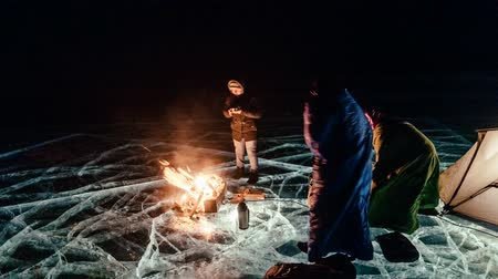 iceberg : Three travelers by the fire right on the ice at night. Campground on ice. The tent stands next to the fire. People are warming themselves by the fire. Time-lapse with a circular motion. The Lake Baikal. Still in the frame there is a car.