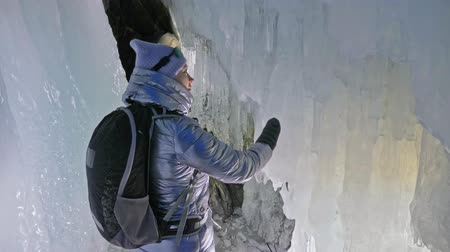 fur boots : Travel woman on ice cave of Lake Baikal. Trip to winter island. Girl backpacker is walking of ice grot. Traveler looks at beautiful ice grotto. Hiker wears sports glasses, silver jacket, backpack, led lamp. Extreme trek and walk of cave in grottoes.
