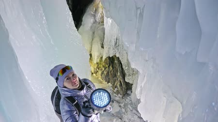 gruta : Travel woman on ice cave of Lake Baikal. Trip to winter island. Girl backpacker is walking of ice grot. Traveler looks at beautiful ice grotto. Hiker wears sports glasses, silver jacket, backpack, led lamp. Extreme trek and walk of cave in grottoes.