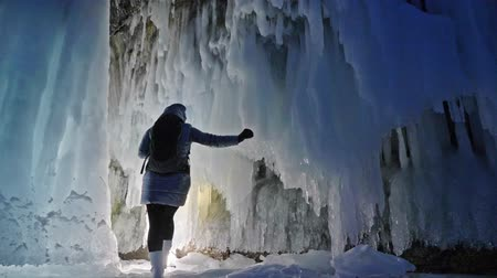 невозделанный : Travel woman on ice cave of Lake Baikal. Trip to winter island. Girl backpacker is walking of ice grot. Traveler looks at beautiful ice grotto. Hiker wears sports glasses, silver jacket, backpack, led lamp. Extreme trek and walk of cave in grottoes.