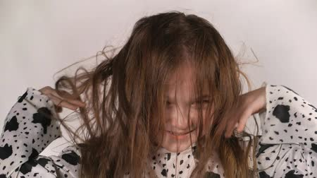 penteado : Happy little girl in the studio on a gray background. She jumps, shows different emotions. Hair fluttering from the wind. Super slow motion, shot at 180fps.