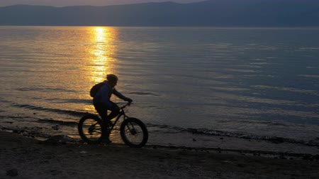 him : Fat bike also called fatbike or fat-tire bike in summer riding in the beach. The athlete passes in a frame silhouette against a beautiful sunset on the sea. Rides directly against the background of reflection.