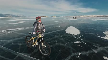 racers : Woman is walking beside bicycle on the ice. The girl is dressed in a silvery down jacket, backpack and helmet. Ice of the frozen Lake Baikal. The tires on the bicycle are covered with special spikes. The traveler is ride a cycle. Stock Footage
