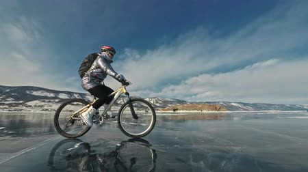 extremo : Woman is riding bicycle on the ice. The girl is dressed in a silvery down jacket, cycling backpack and helmet. Ice of the frozen Lake Baikal. The tires on the bicycle are covered with special spikes. The traveler is ride a cycle.