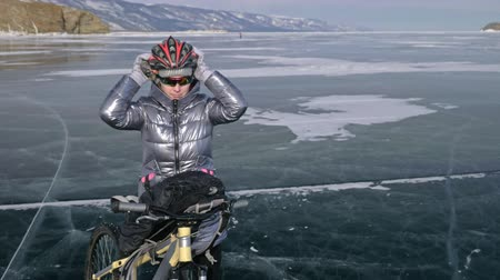 frozen lake : Woman is wearing sports equipment. The girl is dressed in a silvery down jacket, cycling backpack and helmet. Ice of the frozen Lake Baikal. The tires on the bicycle are covered with special spikes. The traveler is ride a cycle.
