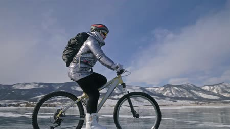 mtb : Woman is riding bicycle on the ice. The girl is dressed in a silvery down jacket, cycling backpack and helmet. Ice of the frozen Lake Baikal. The tires on the bicycle are covered with special spikes. The traveler is ride a cycle.