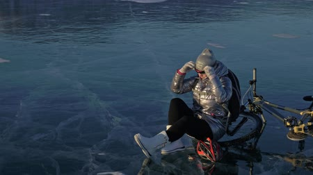 frozen lake : Woman is riding bicycle on the ice. The girl is dressed in a silvery down jacket, cycling backpack and helmet. The cyclist stopped to rest. She sits on the wheel and enjoys the beautiful view of the sunset. The traveler is ride a cycle.