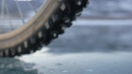 spikes : View of the tire. Shooting 180fps. Woman is riding bicycle on the ice. Ice of the frozen Lake Baikal. The tires on the bicycle are covered with special spikes. The traveler is ride a cycle.