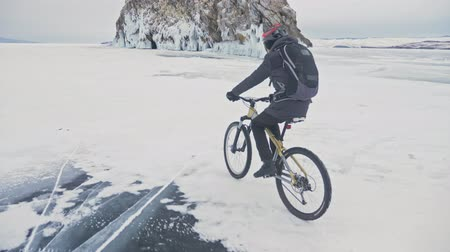 sağlam : Man is riding bicycle near the ice grotto. The rock with ice caves and icicles is very beautiful. The cyclist is dressed in gray down jacket, cycling backpack and helmet. The tires on covered with special spikes. The traveler is ride cycle.