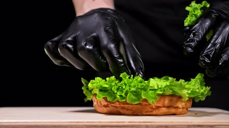 gombák : Burger is cooking on black background in black food gloves. Very luscious air bun and marbled beef. Restaurant where each burgers is cooked by hand. Not made ideal. Not conveyor. Looks real, loving hand made. Put a salad lettuce on a bun. Stock mozgókép