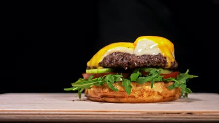 ebruli : Burger is cooking on black background in black food gloves. Very luscious air bun and marbled beef. Restaurant where each burgers is cooked by hand. Roasted steak and onion rings grill in breadcrumbs is placed on the bun. Looks real loving hand made.