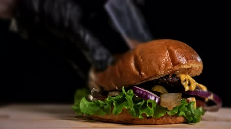 резать : Burger is cooking on black background in black food gloves. Very luscious air bun and marbled beef. Restaurant where each burgers is cooked by hand. Burger cut on the table with a knife. Not made ideal. Not conveyor. Looks real, loving hand made.
