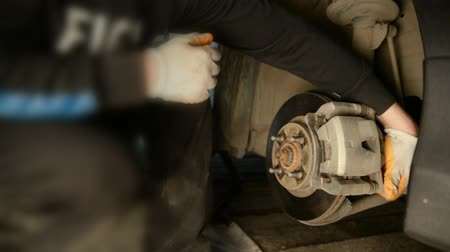 brake : Auto mechanic working on brakes in a car repair shop domestic garage. Professional repair of a car. Stock Footage