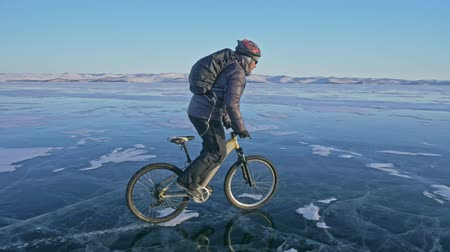 sağlam : Man is riding a bicycle on ice. The cyclist is dressed in a gray down jacket, backpack and helmet. Ice of the frozen Lake Baikal. The tires on the bicycle are covered with special spikes. The traveler is ride a cycle.