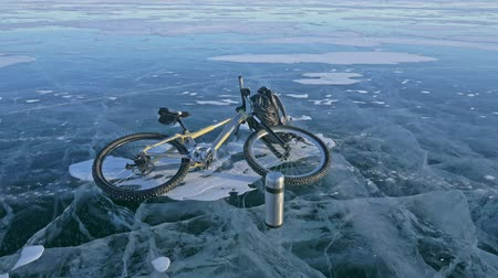 enduro : Man and his bicycle on ice. He looks at the beautiful ice in the cracks. First-person view. The cyclist is dressed in a gray down jacket, backpack and helmet. Ice of the frozen Lake Baikal. The tires on the bicycle are covered with special spikes.