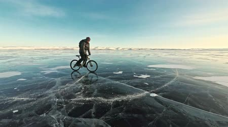 с шипами : Man is riding a bicycle on ice. The cyclist is dressed in a gray down jacket, backpack and helmet. Ice of the frozen Lake Baikal. The tires on the bicycle are covered with special spikes. The traveler is ride a cycle.