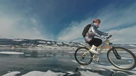 местность : Woman is riding bicycle on the ice. The girl is dressed in a silvery down jacket, cycling backpack and helmet. Ice of the frozen Lake Baikal. The tires on the bicycle are covered with special spikes. The traveler is ride a cycle.